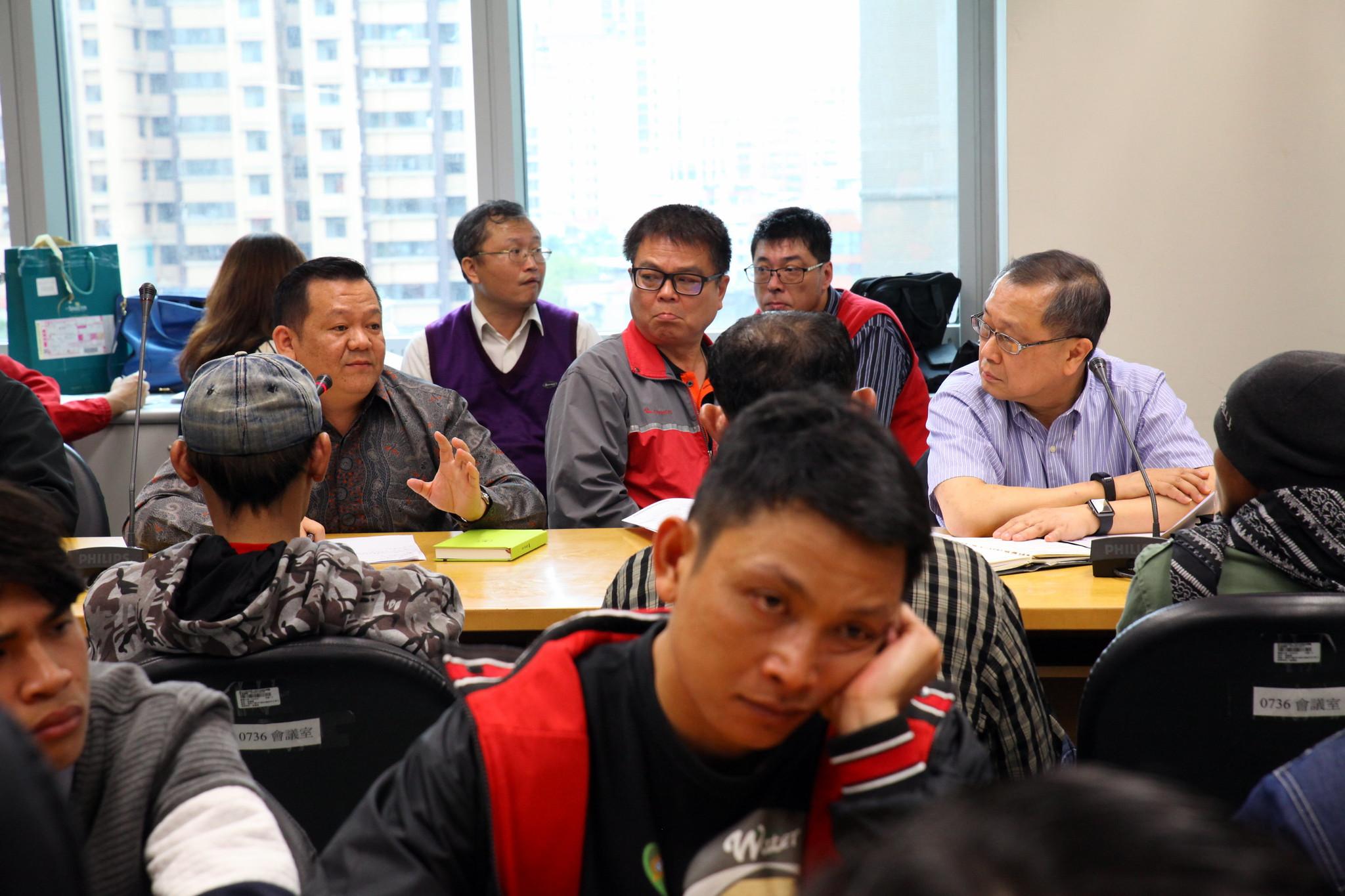 協調會過程,最前方無奈表情者為移工,後方右邊藍色襯衫為人力仲介揚運的董事長高壽濤。(攝影:陳逸婷)