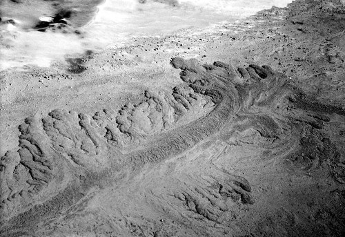 Black and white photo of pyroclastic flow deposits lying atop earlier deposits. The middle of the flow is a thick, dark line, with feathery curls radiating away from the sides and terminous.