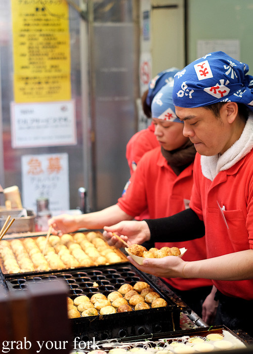 Cooking takoyaki octopus balls at Shinsaibashi, Osaka, Japan