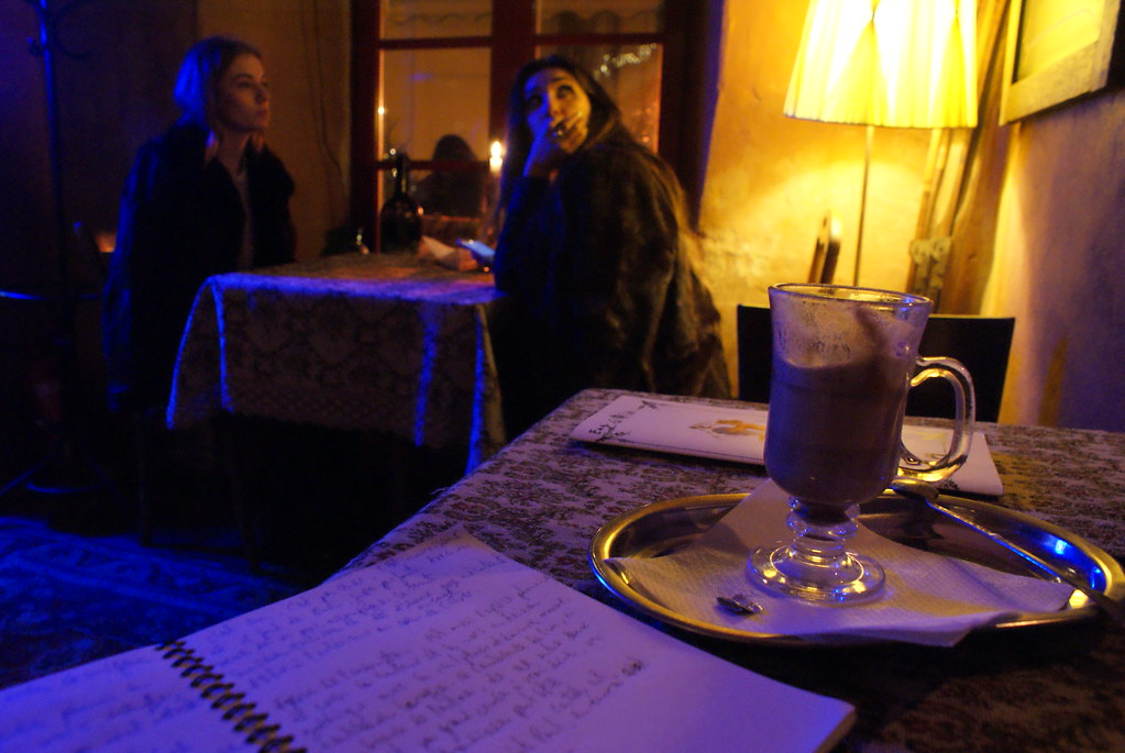 Dans le café 1 en train d'écrire avec un chocolat chaud.