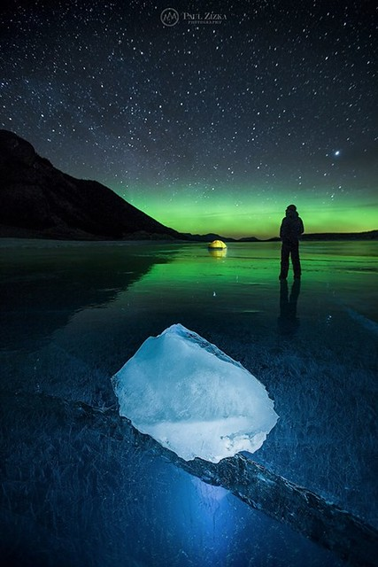 """Alberta Magic."" A windy night out on the frozen Abraham Lake exploring the surreal cracks and ice formations as the aurora glow above illuminated the ice. Self-portrait. Manfrotto Imagine More * I'm currently off the grid shooting in Antarctica with One"