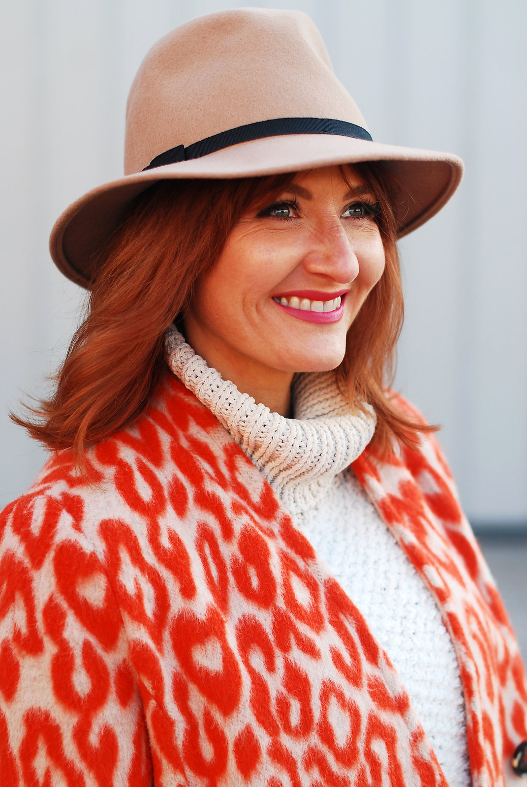 Bold, bright winter outfit: Orange animal print coat  chunky white roll neck sweater  camel wide leg trousers (pants)  white Stan Smiths  red tote bag  camel felt fedora | Not Dressed As Lamb, over 40 style