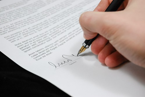 Someone holding a pen signing a contract.