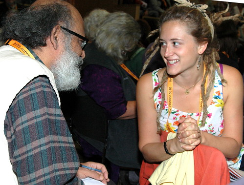 At a conference a young blonde woman talks to older man with smiles