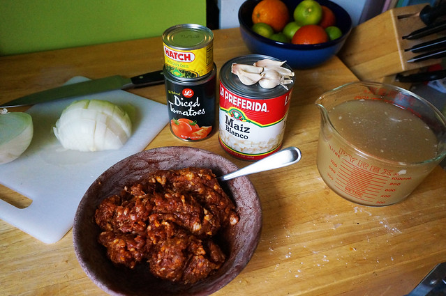 Ingredients: a large can of hominy, cans of tomatoes and chiles, and a bowl heaped with dark red-spiced chorizo