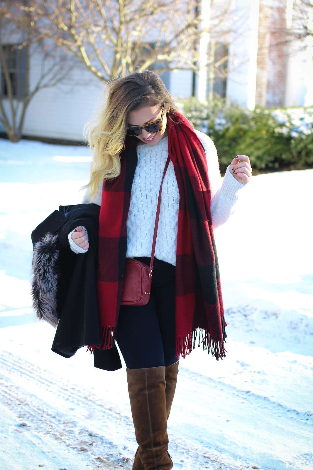 Casual winter outfit in snow. White cable knit sweater, red plaid blanket scarf, OTK brown suede boots.