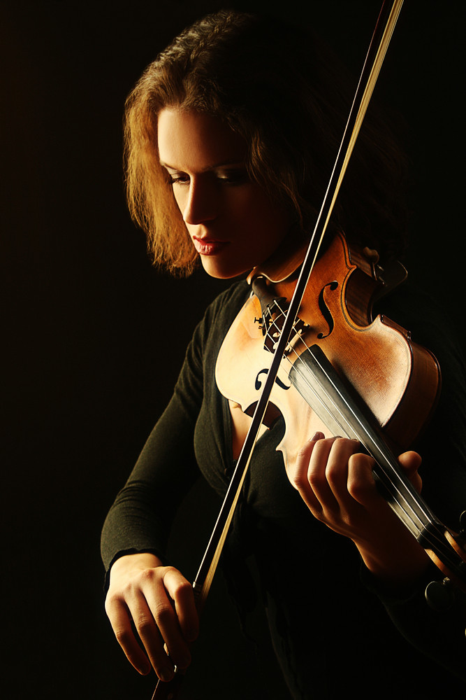 photo of woman playing a violin
