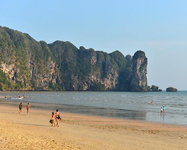 Playa de Ao Nang al atardecer con gente paseando sobre la orilla