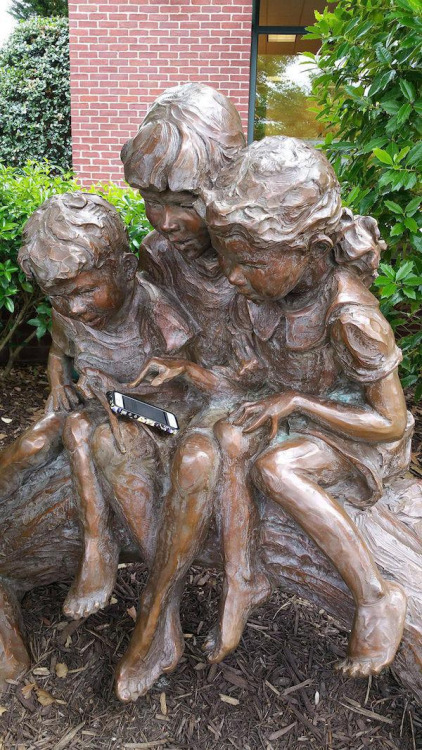 foto graciosa de estatua infantil jugando con el móvil