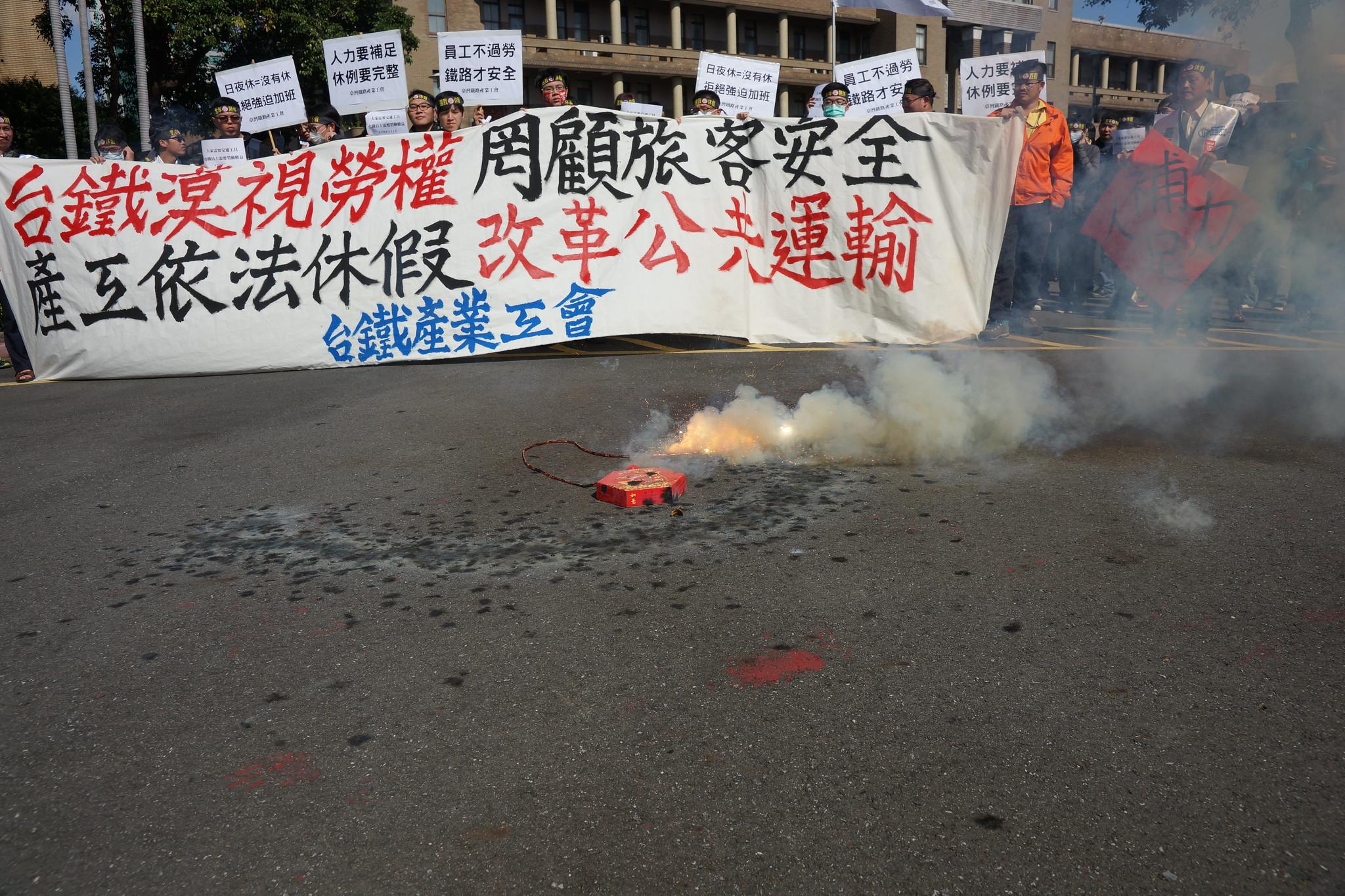"""工会在政院前放鞭炮,希望能赶走""""过劳""""这只年兽。(摄影:王颢中)"""
