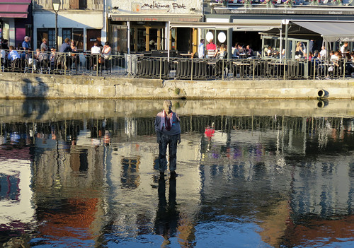 A statue stands in the canal in front of the quay restaurants in Amiens, France