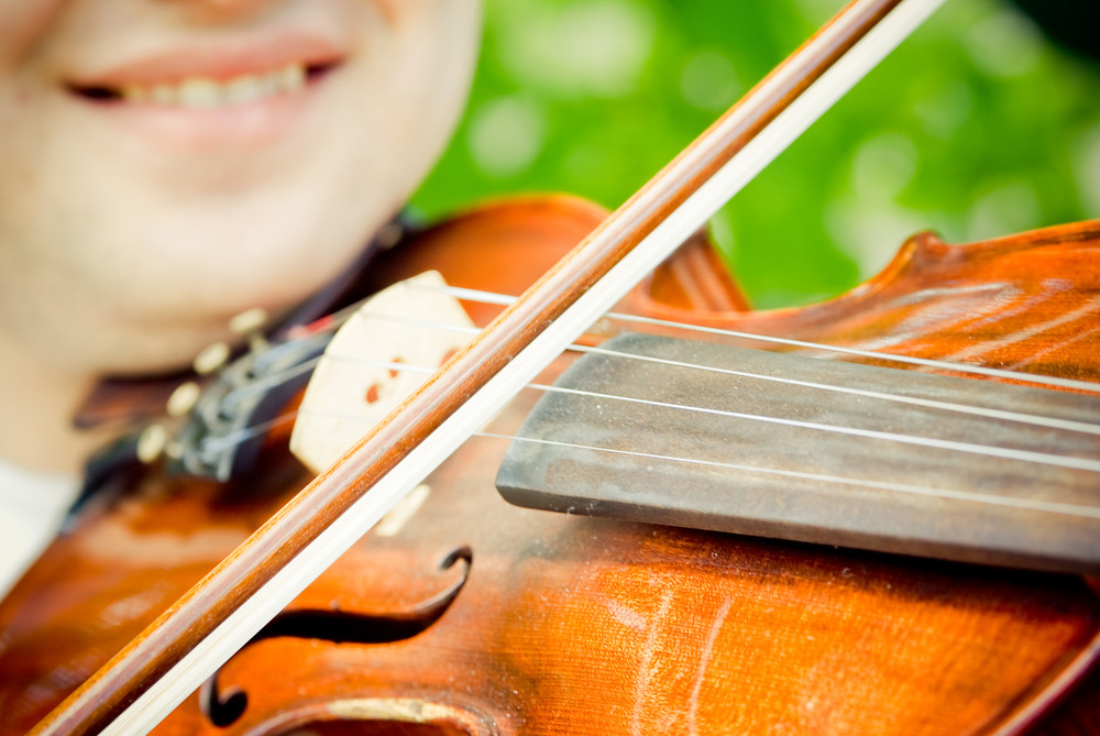 Close-up photo of violinist playfully smiling while playing