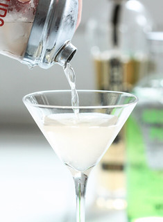 pouring martini into glass from shaker