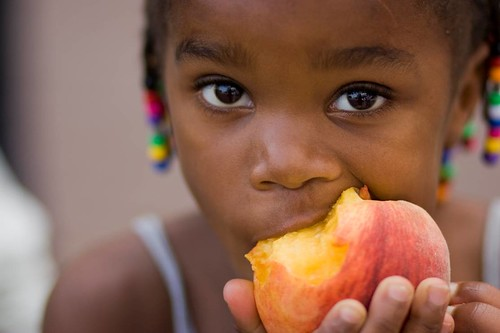 A girl eating a peach