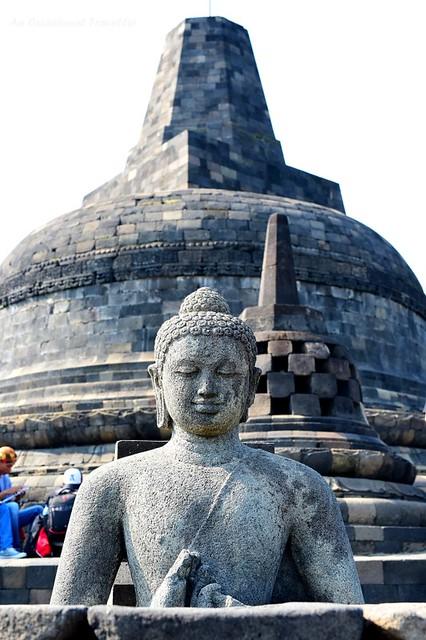 A Buddha statue inside an open stupa