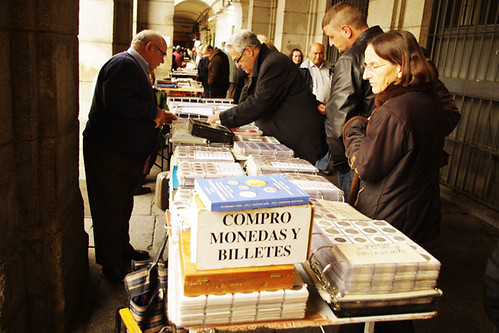 "Madrid5: One of the many sellers at the weekly Sunday flea market under the arcades of the Plaza Mayor. The sign says ""I buy coins and banknotes."""