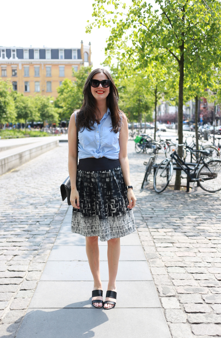 professional outfit: business casual in light blue shirt tied at the waist, abstract printed skirt and mules