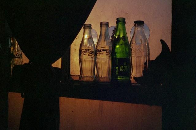 Bottles on window at sunset