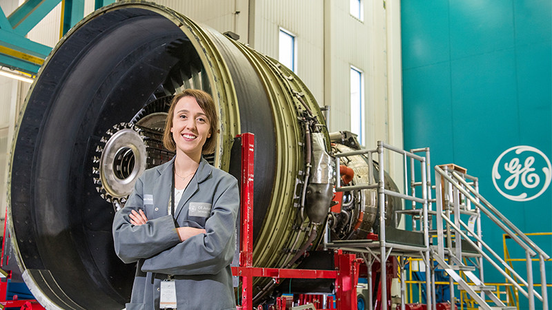 A student stands in front of a gas turbine on placement at GE Aviation