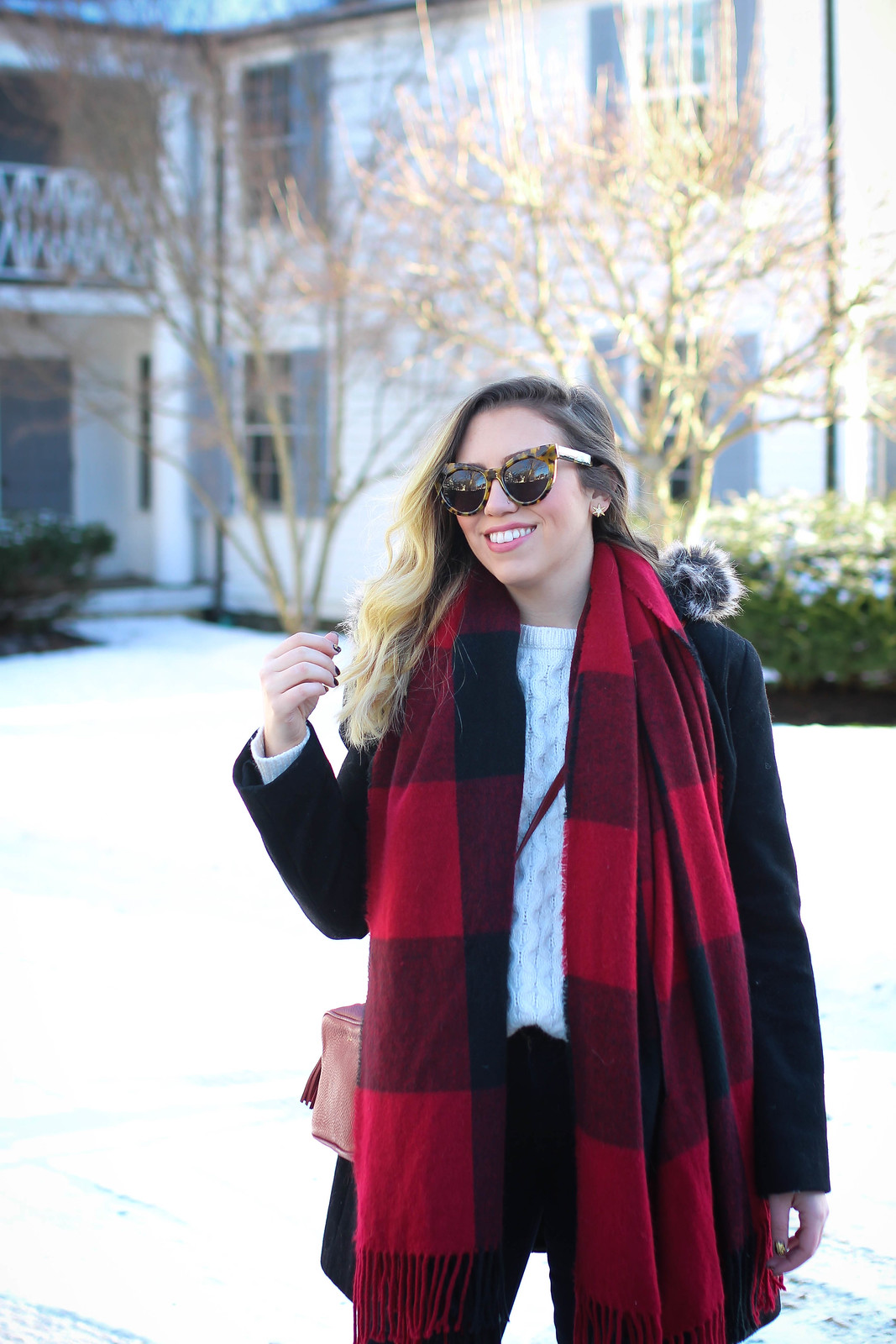 Winter outfit with red plaid blanket scarf, black duffle coat and white cable knit sweater