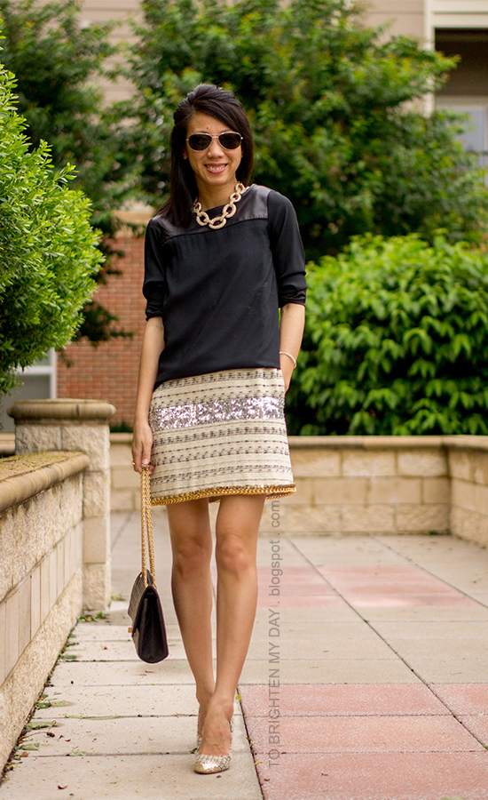 statement necklace, faux leather black top, tweed and sequin dress and pumps