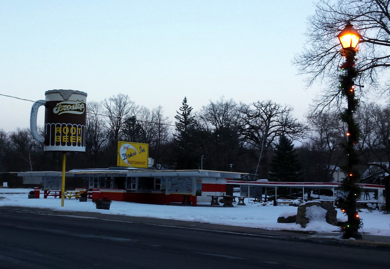 snow-covered Frostop drive-in with a lighted lamppost on the street in front