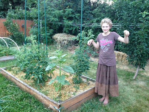 Emma being a tomato plant. She tells me that there are 58 (!) green tomatoes right now.
