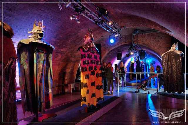 The Establishing Shot: BATMAN: ARKHAM KNIGHT CAPE & COWL EXHIBITION - R-L BATMAN UNDER CONSTRUCTION BY ZEUS, TRIBAL KNIGHTS BY   INKIE & FAR RIGHT ONE FOR ALL, ALL FOR ONE BY NANCY FOUTS - KACHETTE, LONDON