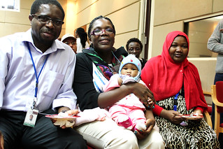 Appolinaire Djikeng, director and Valerian Aloo, capacity building officer pose with Baby BecA and proud mother Rasha Adam, ABCF fellow from Sudan