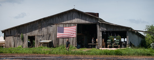 U.S. Marine Corps veteran Calvin Riggleman standing in front of a U.S. flag displayed on a barn on Bigg Riggs farm in Hampshire County, WV