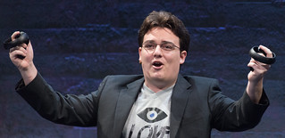 Palmer Luckey (Founder, Oculus) holding up Oculus Touch prototype Half Moon at Step into the Rift | by eVRydayVR
