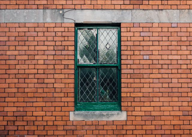 green latticed window against brick wall