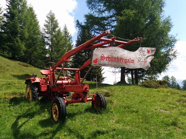 Ein alter Traktor mit dem Wegschild vor der Schönberg Alm