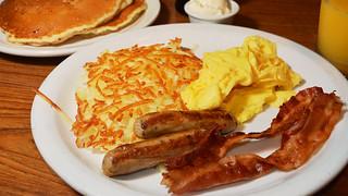 Scrambled eggs, hashbrowns, sausage, bacon, orange juice ...