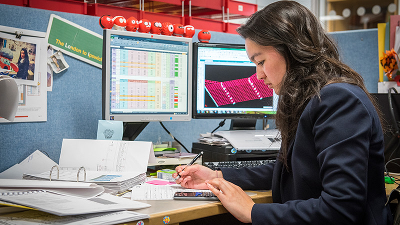 Junshi works at her desk on placement at Mott MacDonald