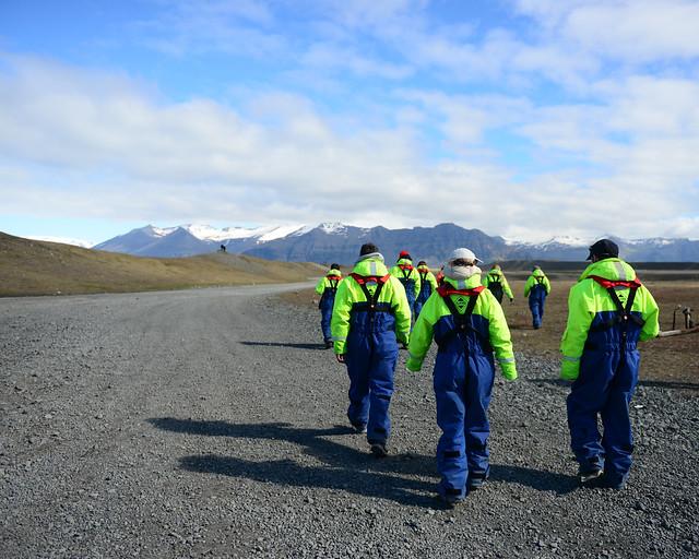 Todo el grupo caminando en pelotón con los trajes térmicos reflectantes de color verde