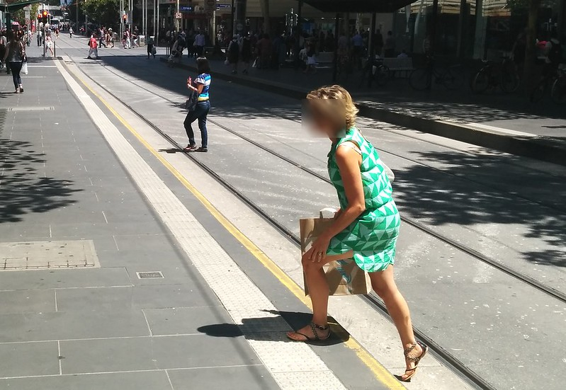 People crossing between tram platforms in Bourke Street
