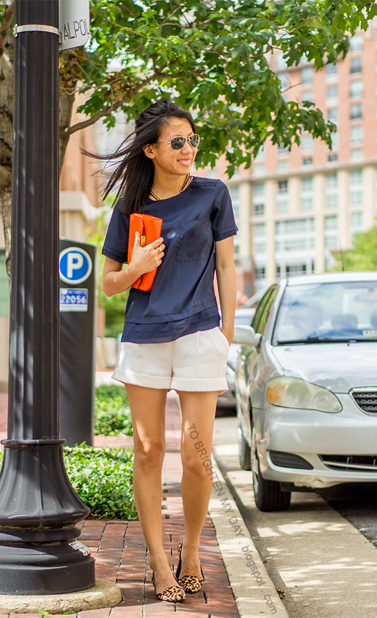 navy layered top, white pleated shorts, orange clutch, leopard flats