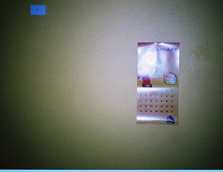 Grainy photo of yellow wall, calender, switch | by Matthew Paul Argall