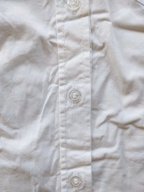 A buttonband on a white button up shirt.