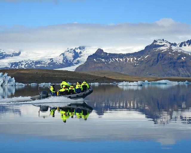 Paseo en barco por la laguna de Jökulsárlón con las montañas nevadas al fondo y el agua como un espejo