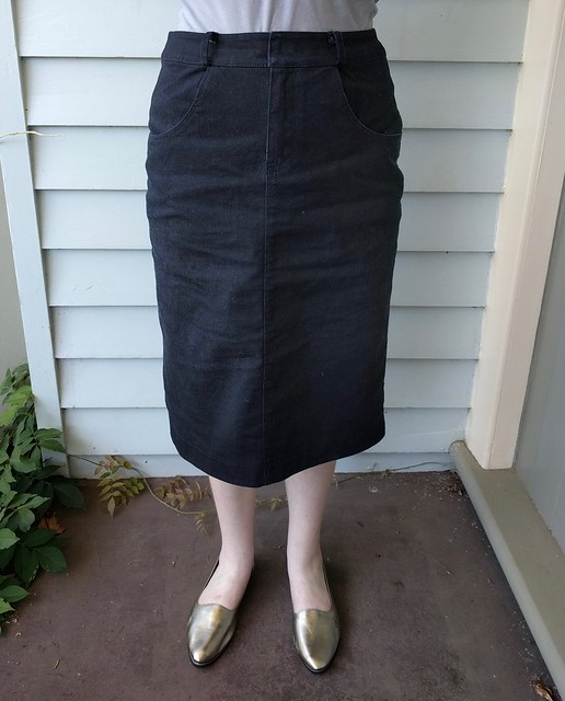 A woman wears a straight black denim skirt and gold shoes.