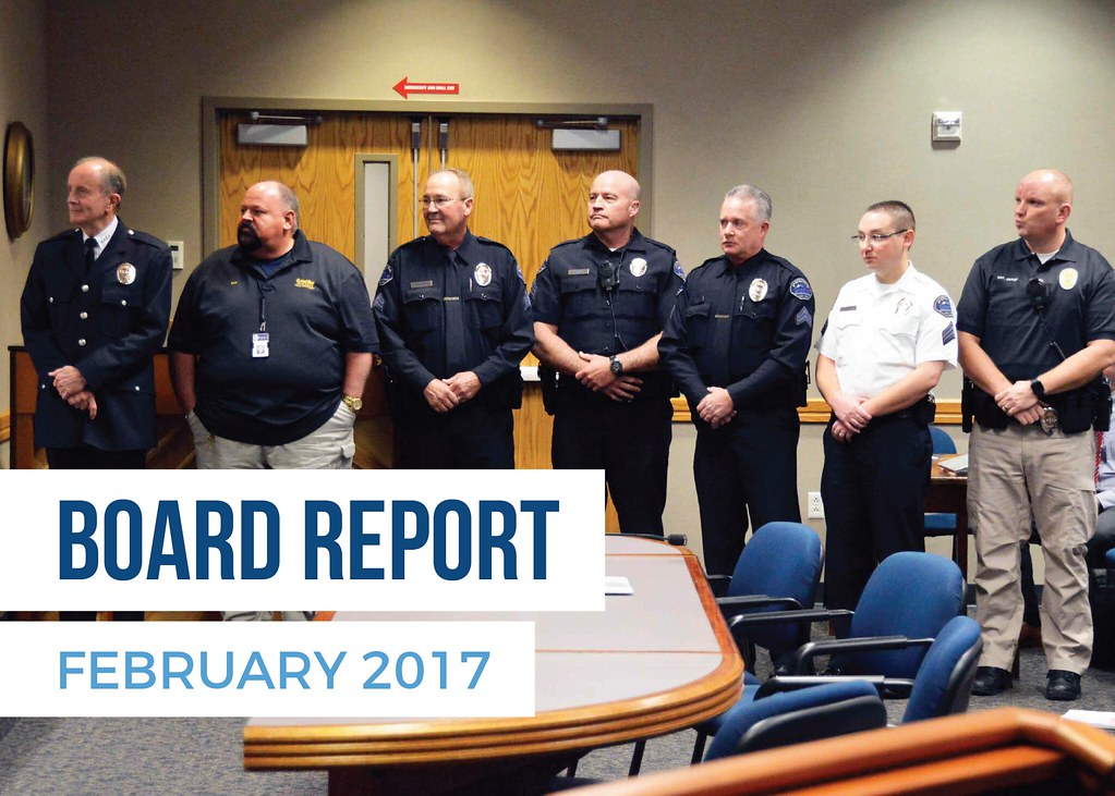 Police officers standing to be recognized during board meeting with text 'Board Report February 2017'