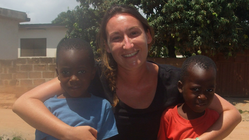 Charlie Young with two children on her placement in Ghana