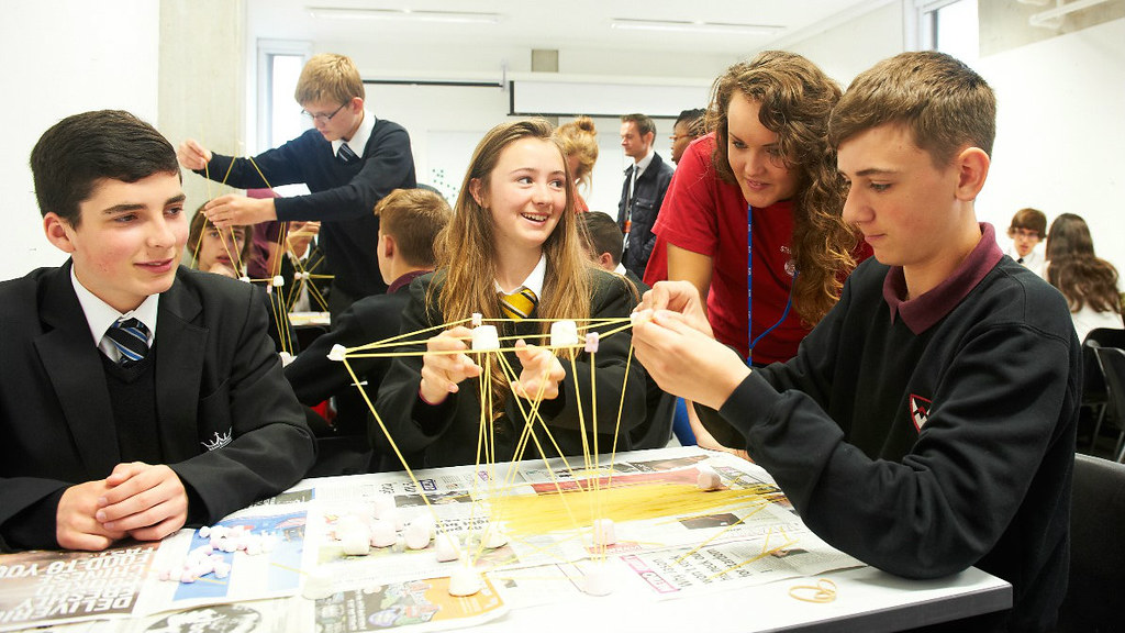 School students building a marshmallow and spaghetti tower ata desk with a Student Ambassador