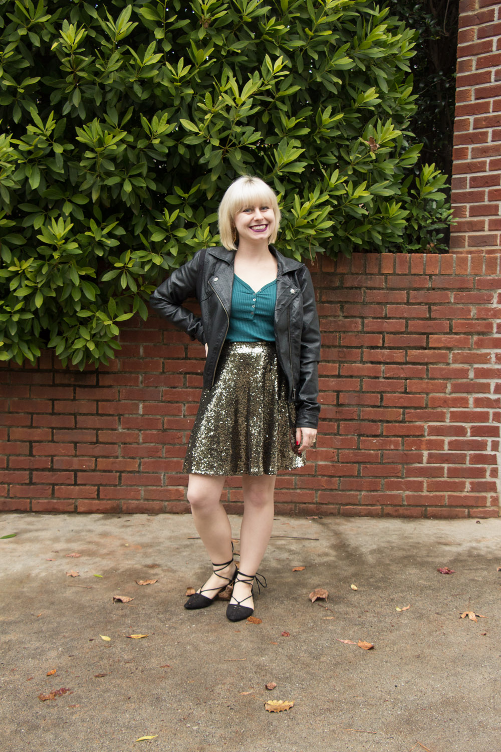Blonde Hair, Leather Jacket, Green Top, Sequined Skater Skirt, and Black Lace Up Shoes