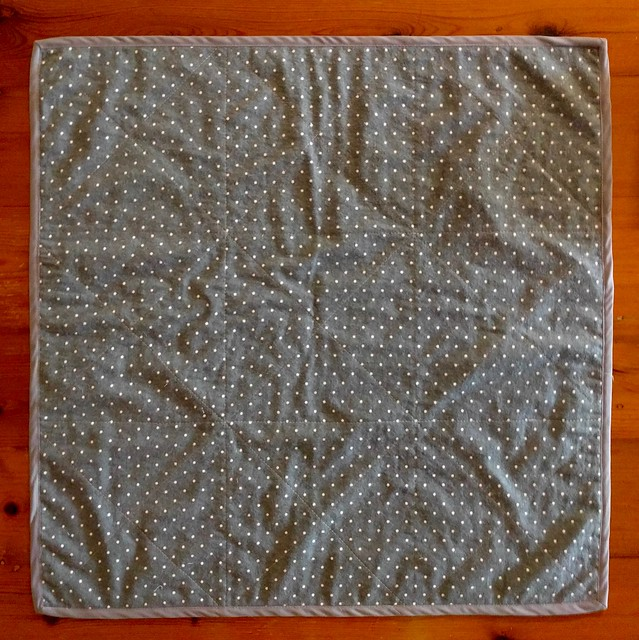 An image of the back of a baby blanket or quilt. It is a simple square made from dark grey flannelette with white pinspots.
