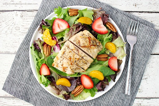This California Chicken Salad is a quick and healthy dinner idea! Grilled chicken is served atop a bed of spring mix lettuce and pairs well with juicy strawberries, sweet Mandarin oranges and toasted pecans for crunch! Serve with Balsamic Vinaigrette.