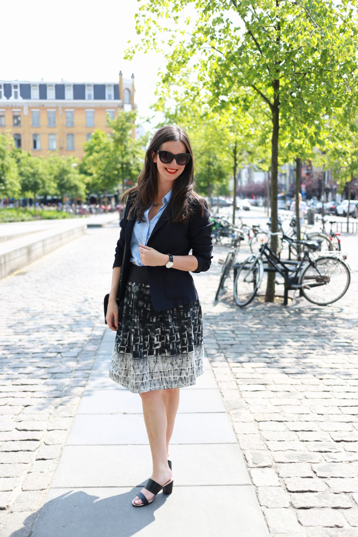 professional outfit: business casual in navy blazer, light blue shirt tied at the waist, abstract printed skirt and mules