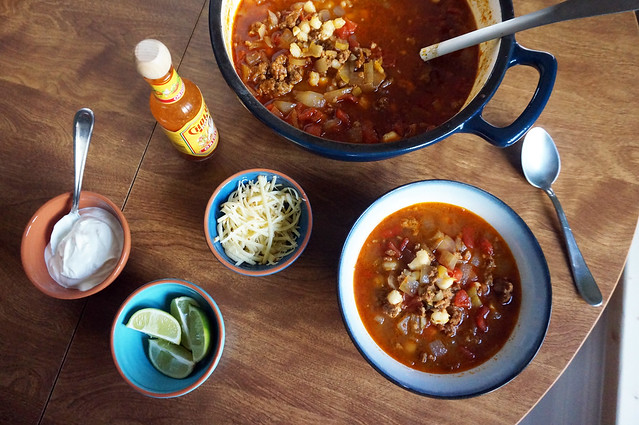 Overhead of a table laden with an enameled cast iron pot filled with pozole, an individual portion of the soup, and accompaniments: hot sauce, shredded cheese, lime wedges, and sour cream.